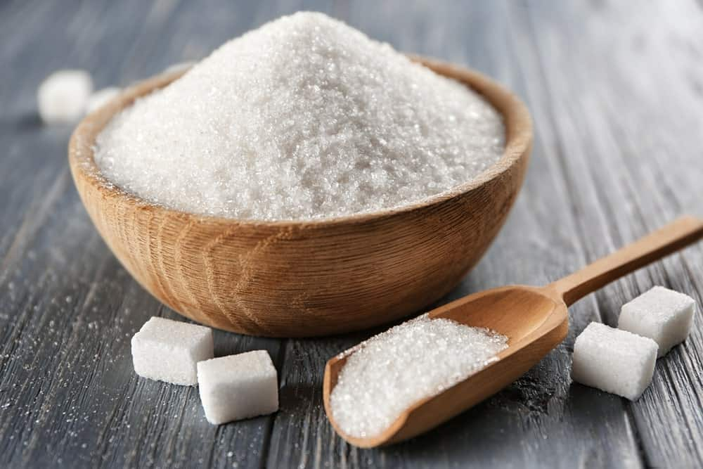 A wooden bowl of sugar along with sugar cubes.