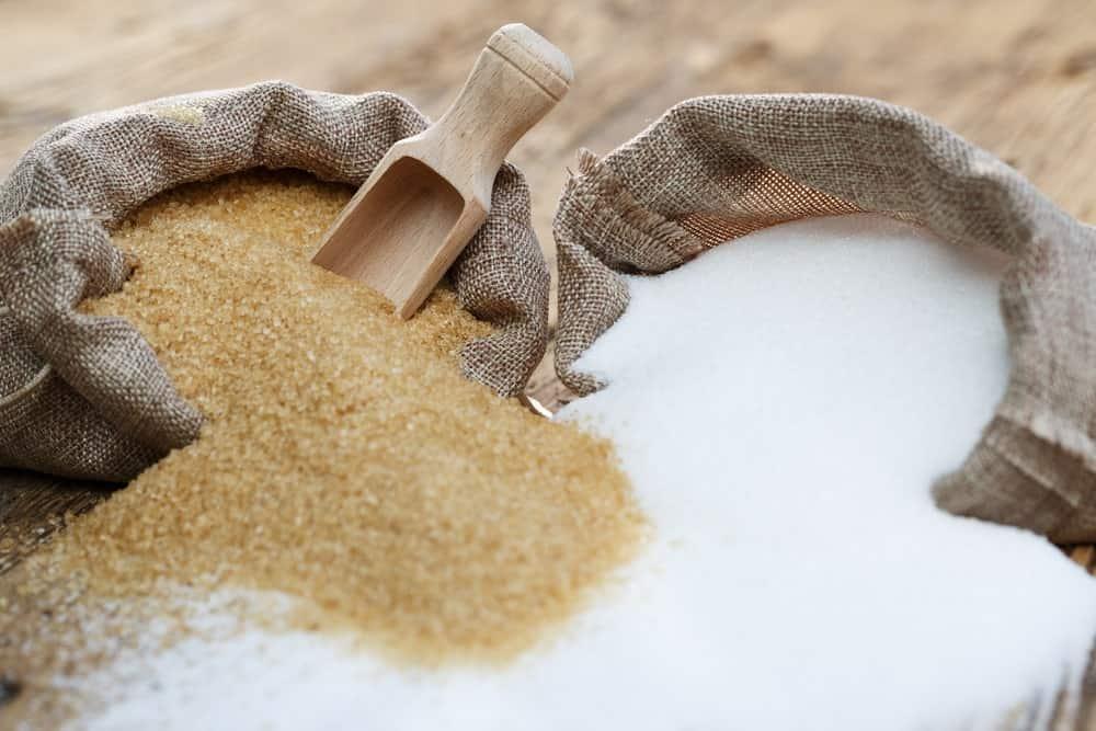 A sack of brown sugar and a sack of white sugar.