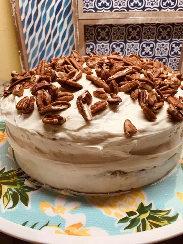 The cake is iced and topped with walnuts.