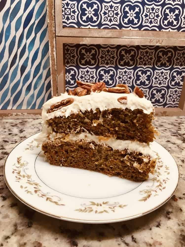 A slice of freshly-baked carrot cake topped with walnuts.
