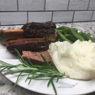 A freshly cooked plate of braised slow cooker short ribs with a side of mashed potatoes and steamed vegetables.
