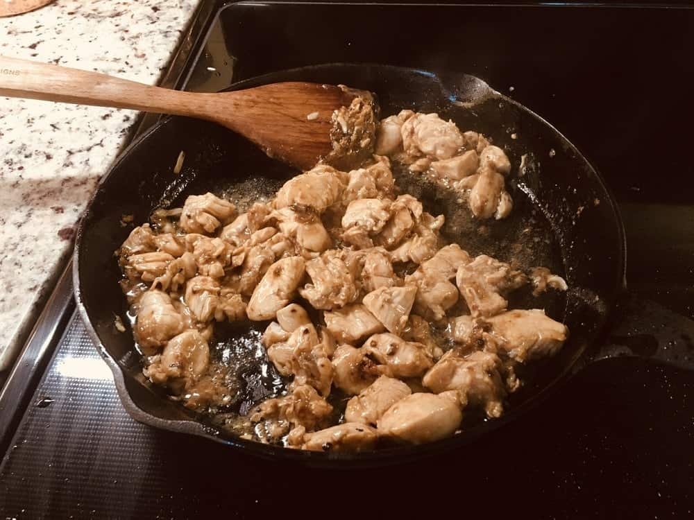The marinated chicken is then added into the skillet with the spices.