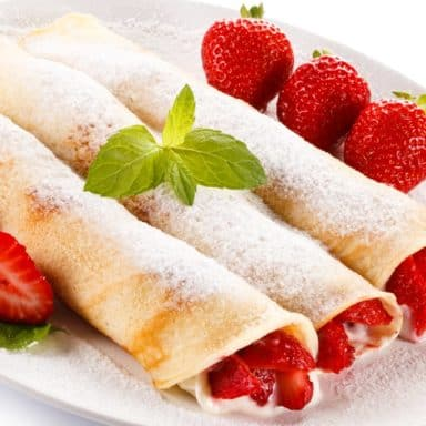 A plate of strawberry cream cheese crepes with fresh strawberry on the side.
