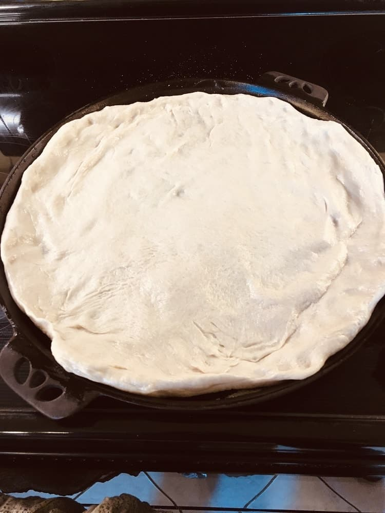 The prepared dough is fixed onto the sides of the skillet.