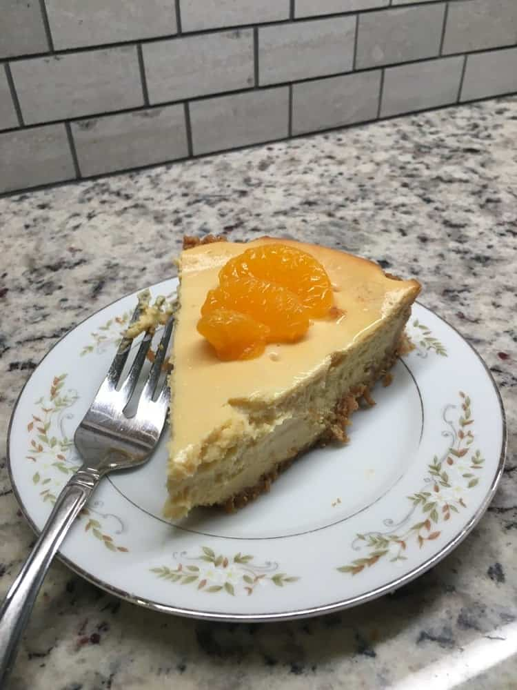 A slice of orange creamsicle cheesecake topped with fresh orange slices.