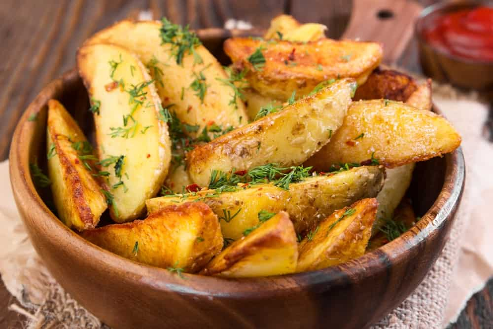 Freshly-made loaded potato wedges in a wooden bowl.