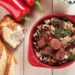 A bowl of freshly-cooked red beans and rice with sausage slices.