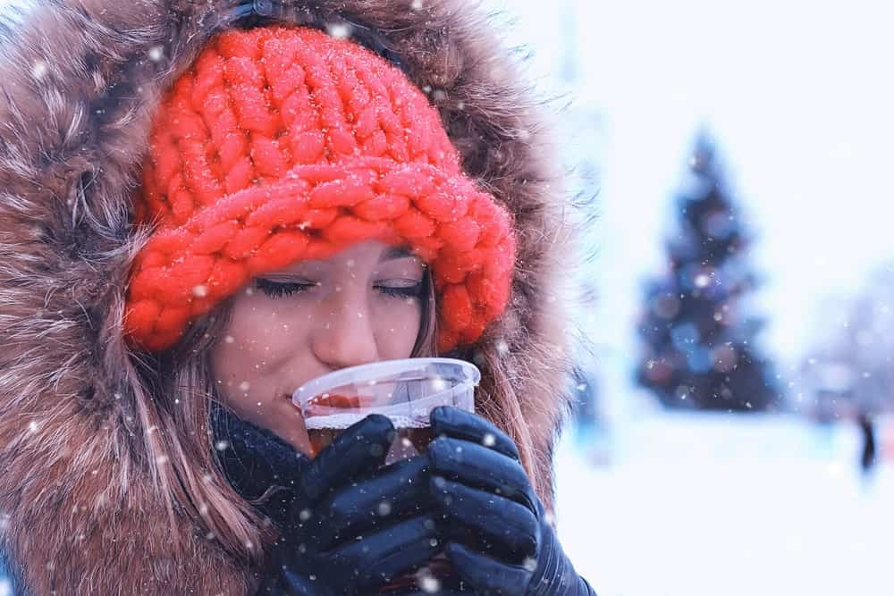 A woman drinking mulled mead at a snowy park.