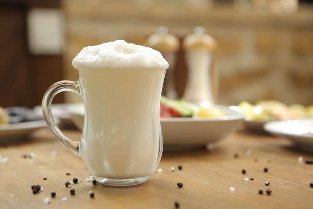 A glass mug of Turkish buttermilk drink.