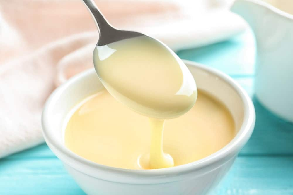 A small bowl of thick and sweetened condensed milk being spooned.