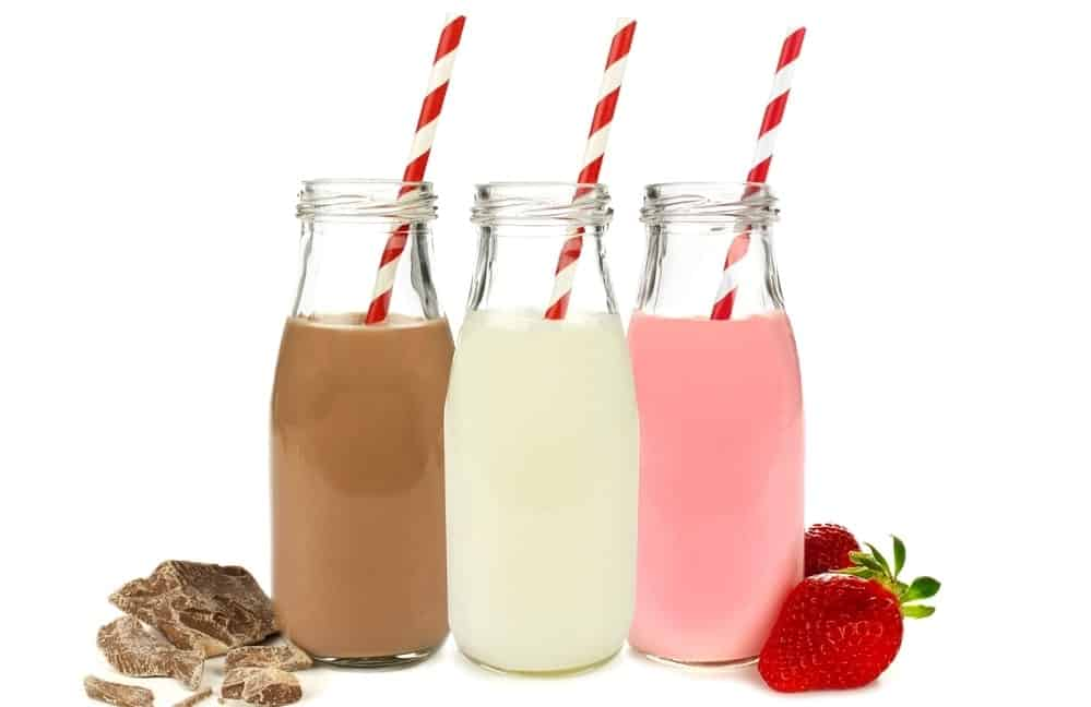 Bottles of flavored milk with striped straws.