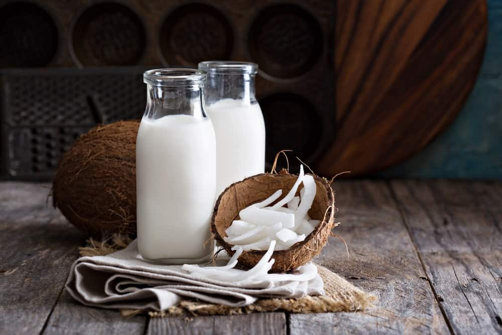 A couple of bottle of coconut milk with fresh coconuts.