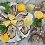 A plate of fresh oysters with slices of lemon.