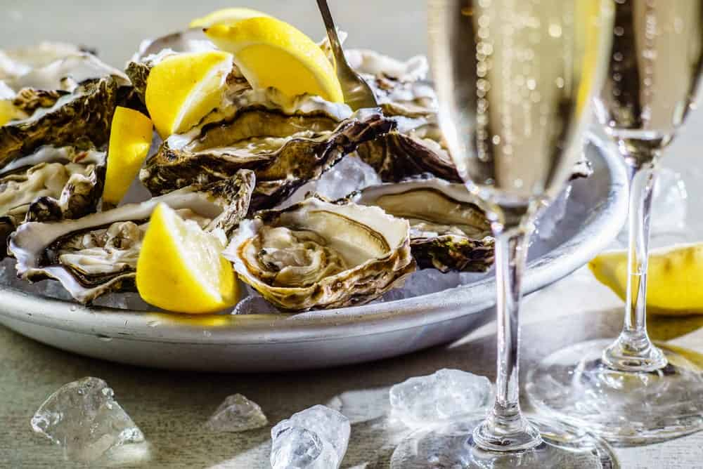 A plate of fresh oysters beside glasses of champagne.