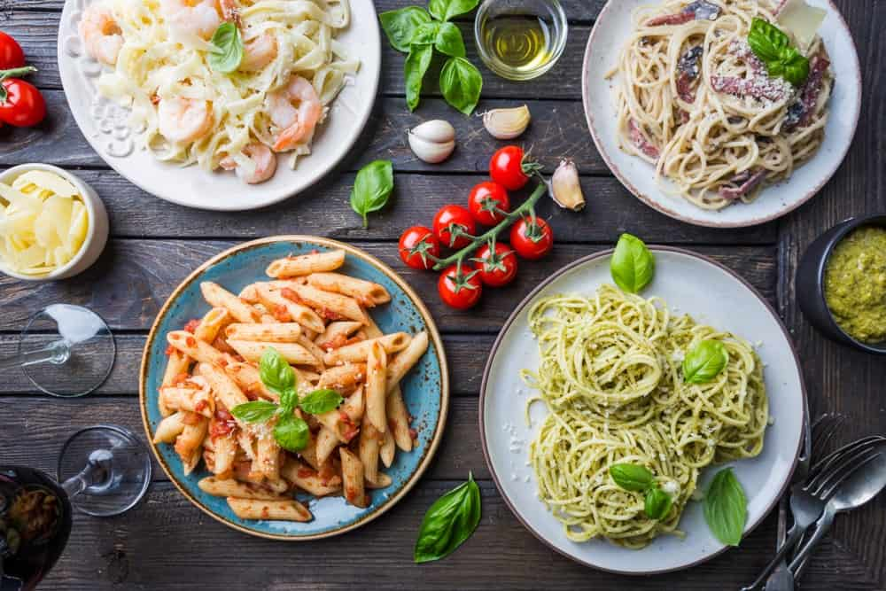 Four varieties of pasta dish on a dark wooden table garnished with fresh ingredients.