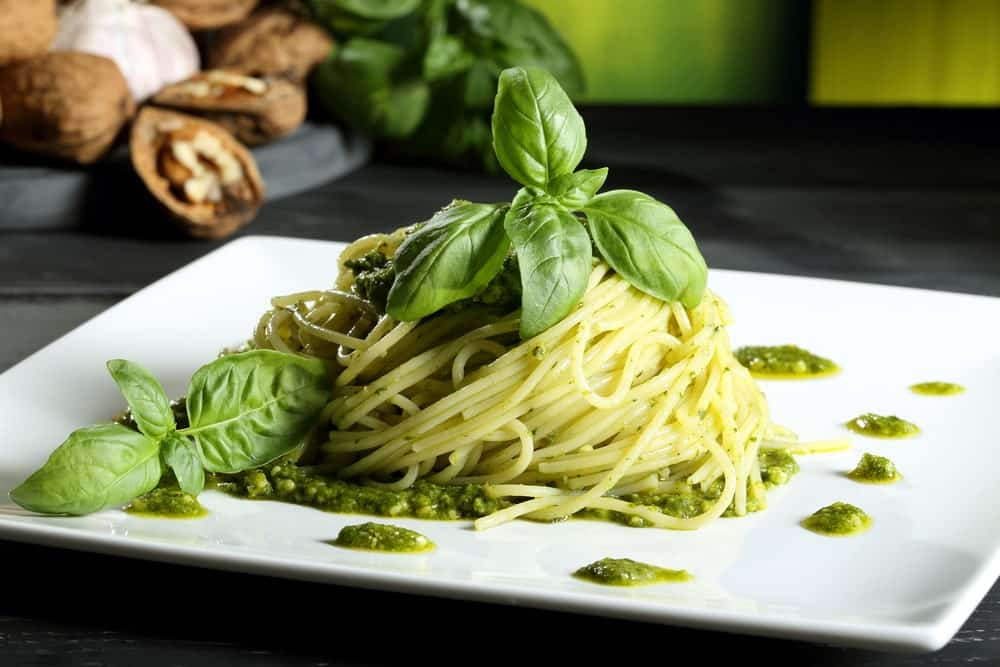 A plate of pesto pasta garnished with fresh basil leaves.