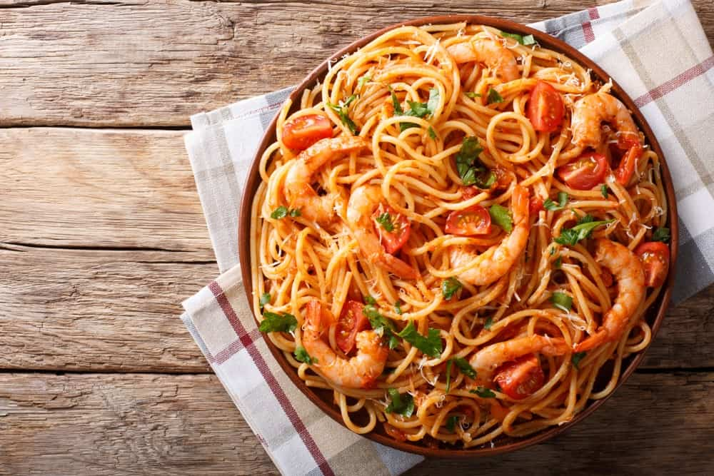 A heaping plate of pomodoro pasta with pieces of shrimp.