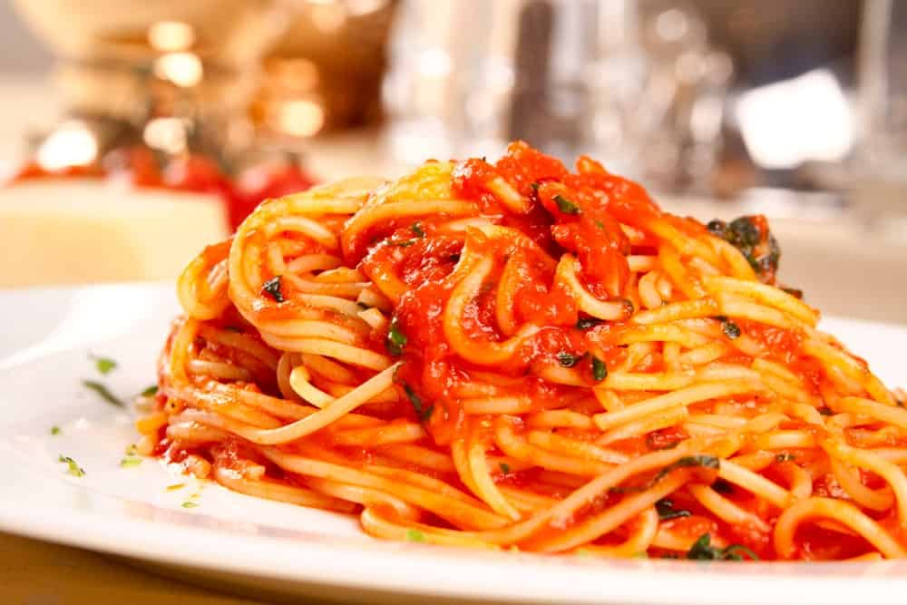 A close look at a plate of marinara pasta.