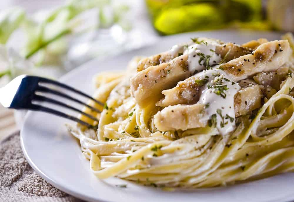 A close look at a plate of freshly-cooked Alfredo pasta with chicken.