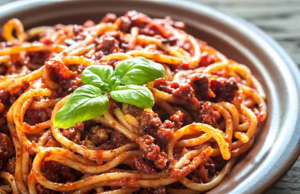 A close look at a plate of Bolognese pasta garnished with fresh basil leaves.