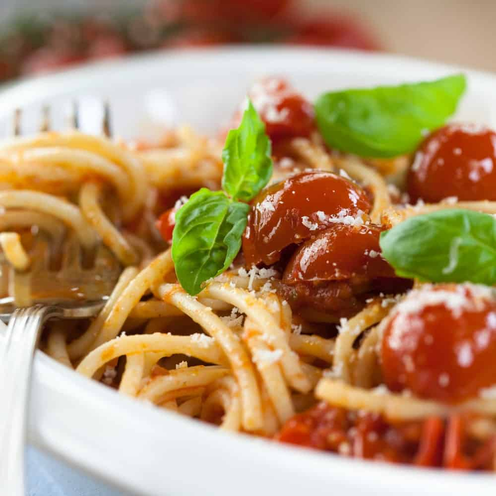 A close look at a plate of roasted tomato pasta with parmesan and fresh basil leaves.