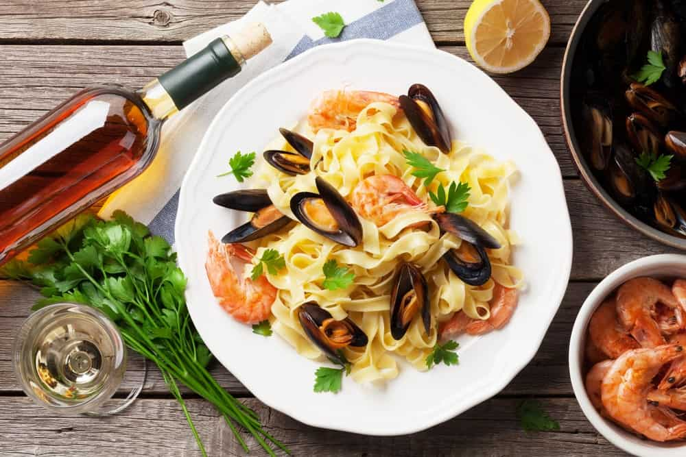 A look at a plate of Frutti di Mare with mussels, shrimp and wine.