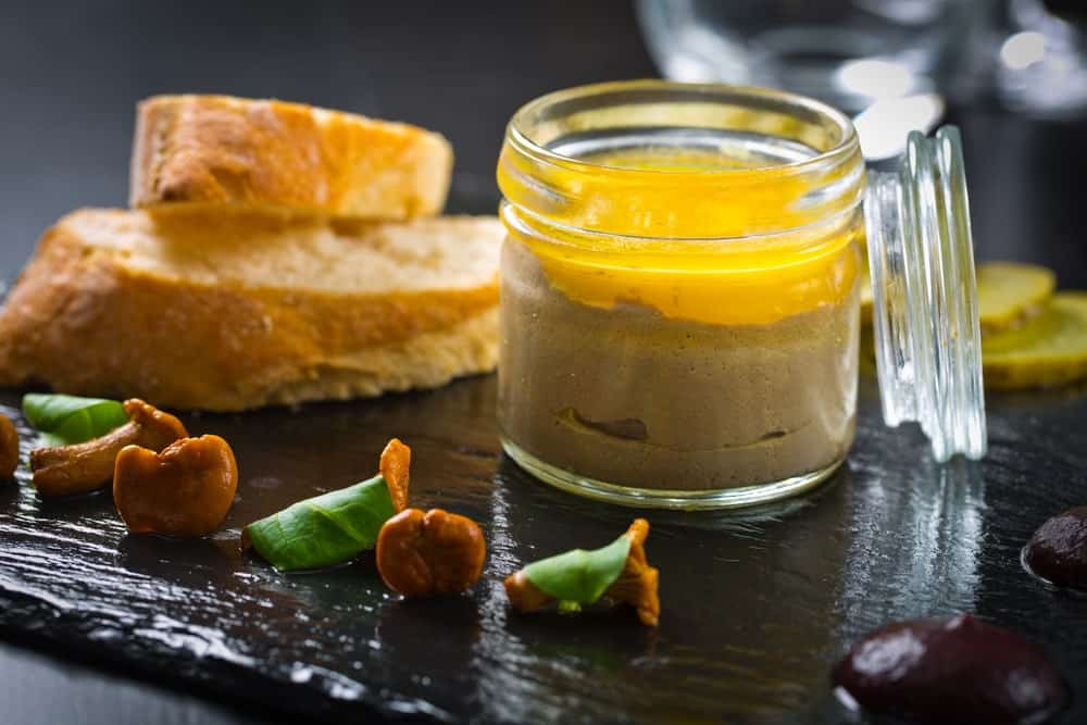 A jar of pate de champagne served with bread.