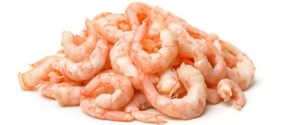 A stack of cooked and peeled pink shrimps.