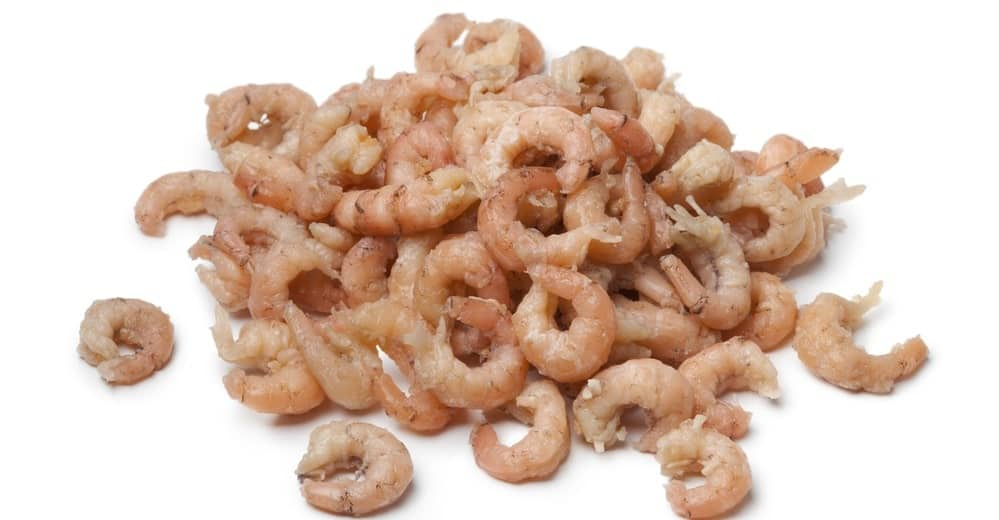 A stack of cooked and peeled brown shrimps.