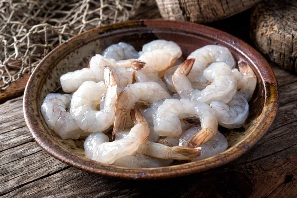A bowl of raw peeled white shrimps.