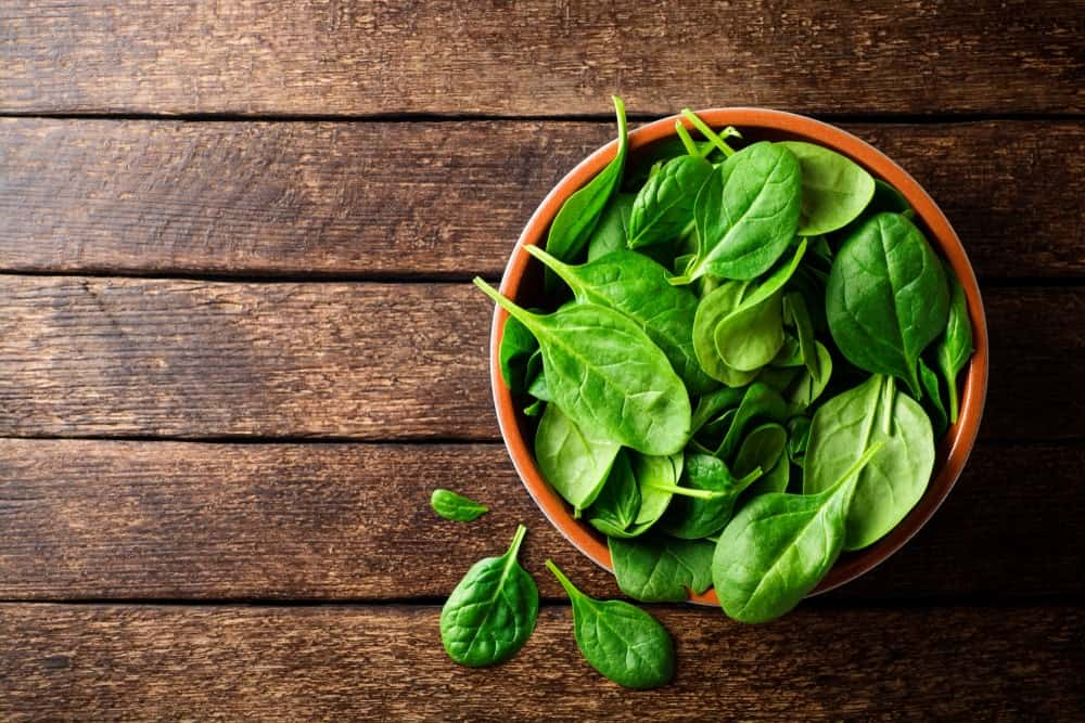 A bowl of fresh spinach on a wooden table.