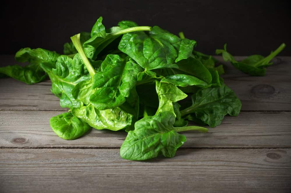 A pile of savoy spinach on a wooden table.