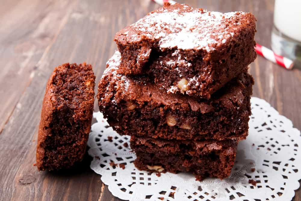 A stack of homemade chunky brownies with nuts.