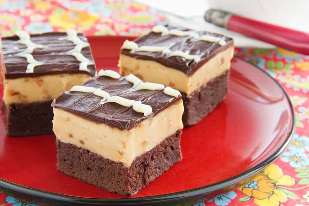 Slices of peanutbutter buckeye brownies on a red plate.