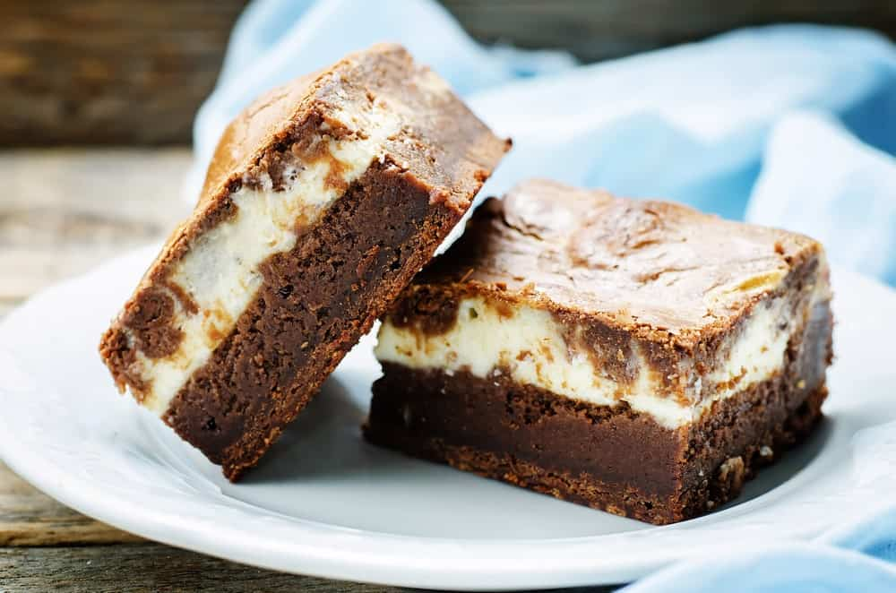 A couple of cheesecake brownies on a white plate.