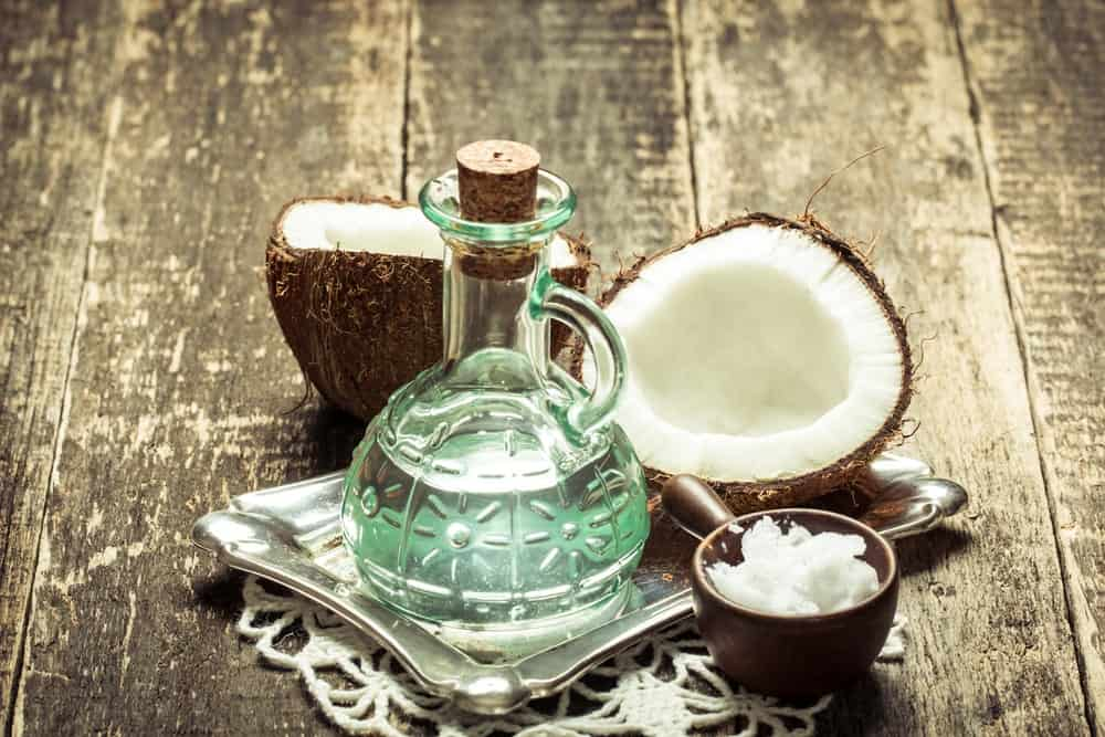 A glass bottle of coconut oil with fresh coconuts.