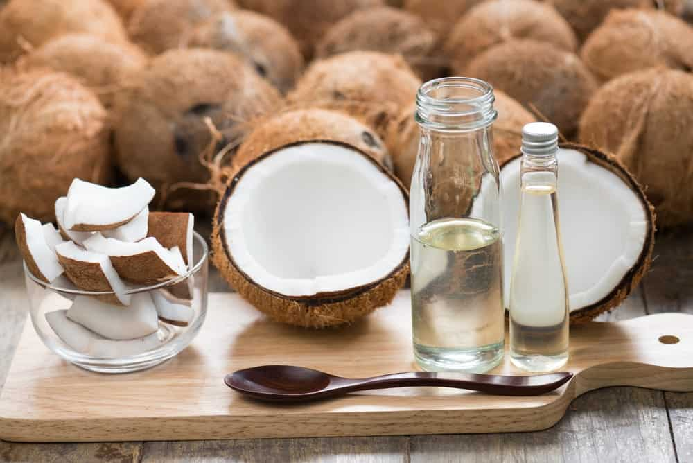 A bottle of refined coconut oil with fresh coconuts.