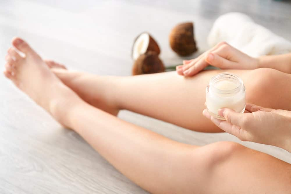 A woman applying coconut oil onto her skin.