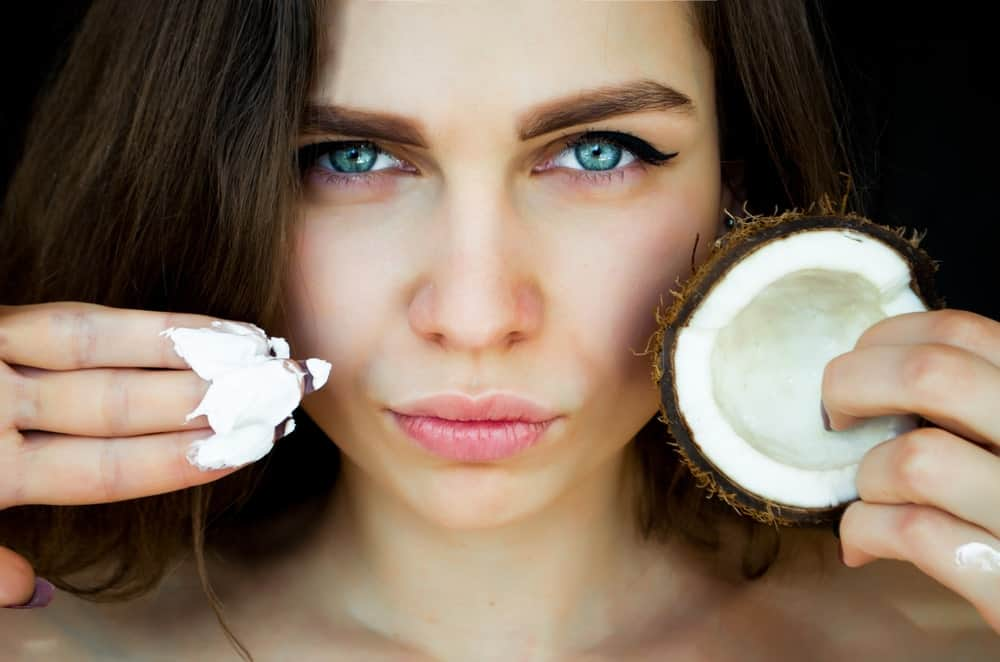 A woman moisturizing her skin with coconut oil.