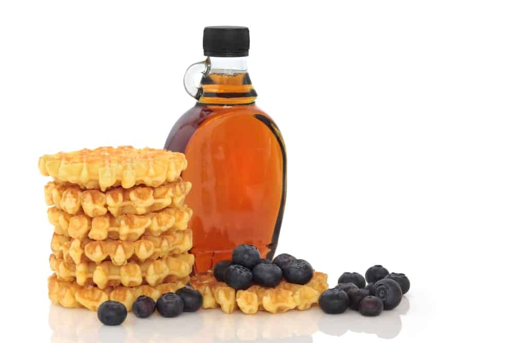 A stack of waffles with a bottle of maple syrup.