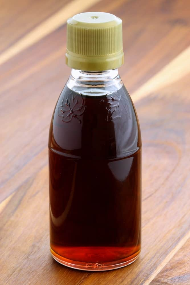 A small bottle of very dark maple syrup.