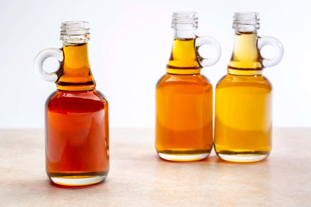Three different types of maple syrups in small bottles.