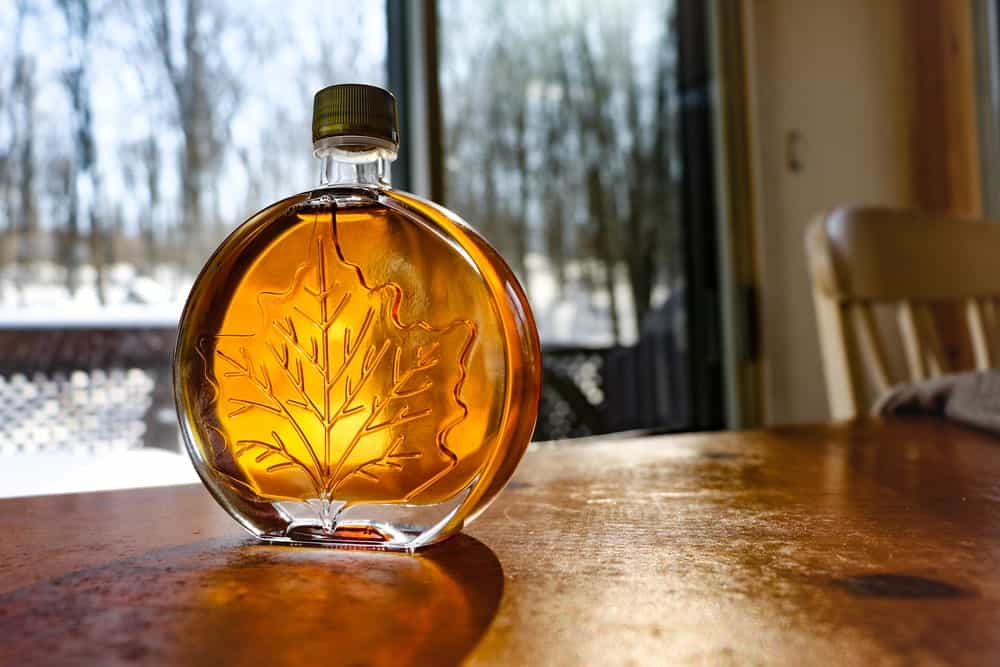 A look at amber maple syrup in a sleek round bottle.
