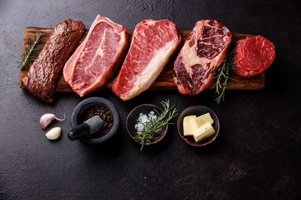 Variety of raw steaks on wooden board along with seasonings.