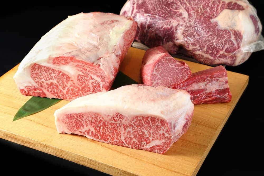 Thick slices of fullblood wagyu tenderloin on a wooden chopping board.