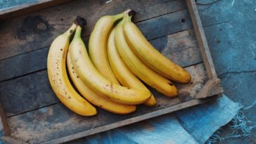 Clusters of ripe bananas on a wooden tray.