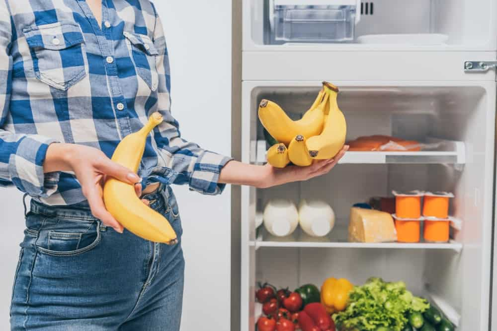 A woman putting the remainder of her bananas into he freezer.