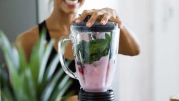 A woman is making a healthy blended smoothie with fruits and spinach.