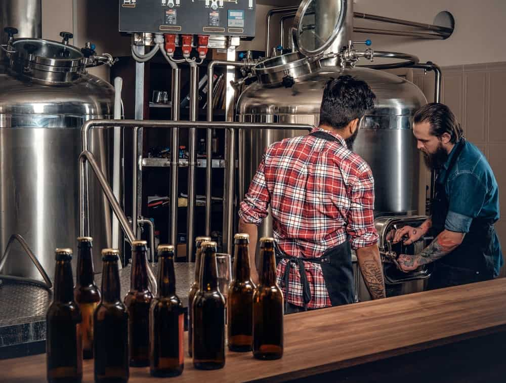 Two men making beer in the craft microbrewery.